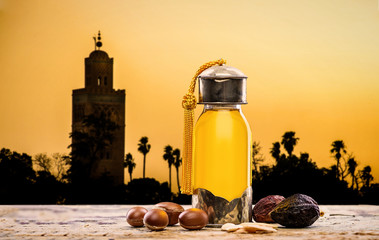 Argan oil and fruits with landscape at sunset