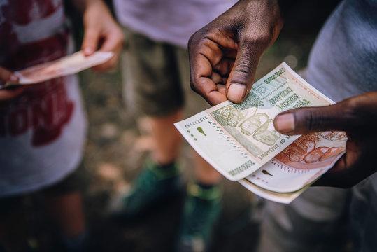 Close up - Händler zählt Geldscheine auf einem Markt in Simbabwe