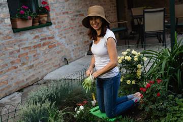 senior woman planting flower in her garden