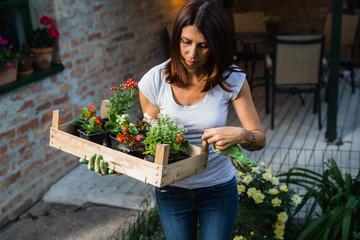 woman holding seedlings in her home garden