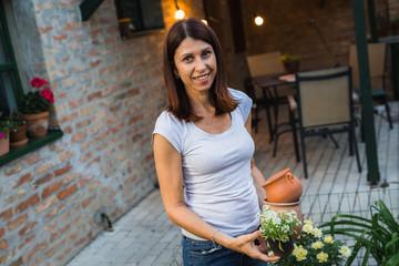 senior woman holding seedlings in her home garden