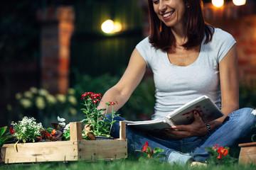 happy woman gardening in her backyard. evening scene