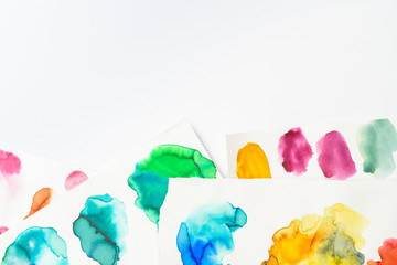 top view of abstract watercolor pink, yellow, green and blue spills on white background