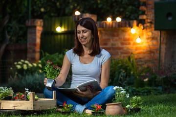 evening scene of woman planting seedlings in her home garden
