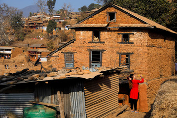 A woman combs her hair outside a village house at Talukachandani village in Nuwakot district