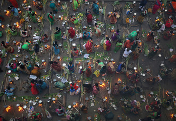 Devotees prepare rice dishes to offer to the Hindu sun god as they attend Pongal celebrations early morning on a roadside in Mumbai