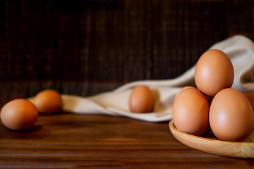 Brown eggs on wooden table with broken and egg yolk.