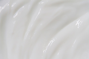 The white surface of the cream lotion softens the background.