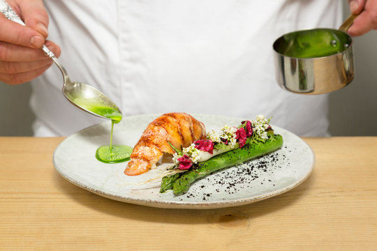 Gourmet chef pouring green sauce on a lobster