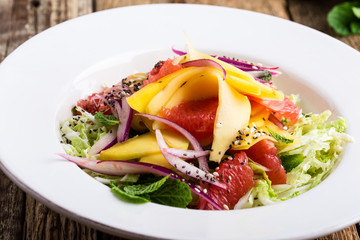 Healthy plant-based meal, salad with mango, grapefruit and cabbage