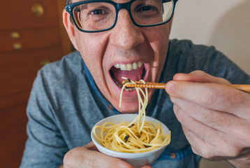 Closeup of man eating spaghetti and crickets with chopsticks