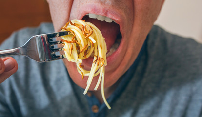 Closeup of man eating spaghetti with crispy worms