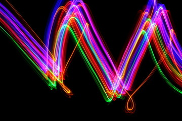 Light painting, long exposure photography, vibrant multi color against a black background