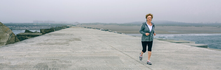 Senior sportswoman with headphones running by sea pier
