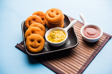 Crunchy potato smily face chips or fried smileys served with ketchup