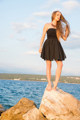 A beautiful woman in an elegant black dress standing and posing on the rocks next to the sea on a sunny day.