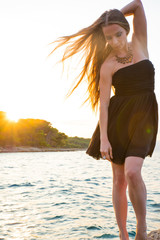 A beautiful woman in an elegant black dress standing and posing on the rocks next to the sea during the sunset.