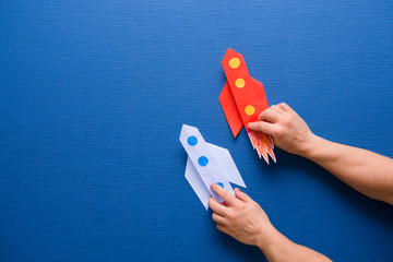 male hands hold a rocket from paper on a blue background
