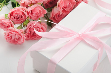 White gift box with a pink ribbon and a bouquet of roses on a white background. A gift for Valentine's Day, birthday, women's day
