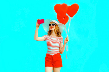 Happy smiling young woman taking selfie picture by phone with red heart shaped air balloons in summer straw hat and shorts on colorful blue background