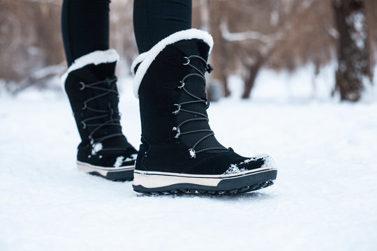Black winter women's boots with white fur and white soles on the snow in the park