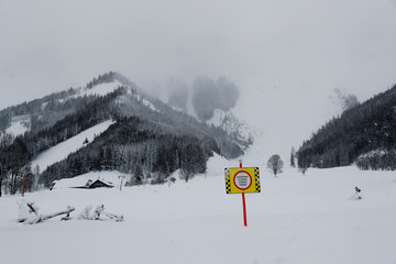 A sign warning of avalanche danger is seen after heavy snowfall in the village of Ramsau