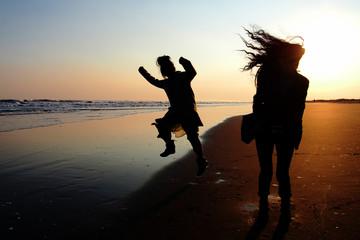 夕焼けの海辺ではしゃぐ女友達