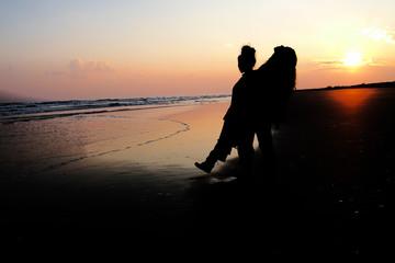 夕焼けの海辺に立つ女友達