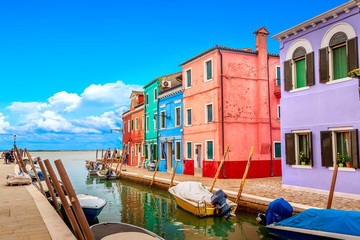 Colorful houses in Burano near Venice, Italy with boats and beautiful blue sky in summer. Famous tourist attraction in Venice. Picture of canal and fishing boats