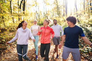 Small group of runners dressed in sportswear talking and walking through woods in autumn. Wall mural