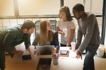 Group of co workers being shown latest presentation by young attractive woman