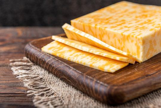 Marble cheese on dark wooden background.