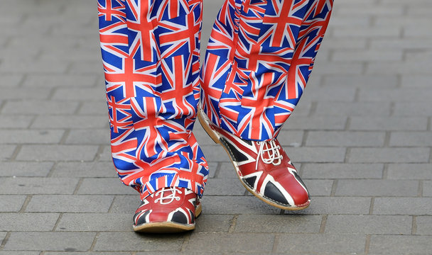 A person wearing trousers and shoes with Union Jack pattern walks outside the Houses of Parliament in London