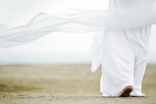 Photo of a man walking in a white robe on the sand. A picture from the back, a person is visible to the waist, clothes are fluttering in the wind