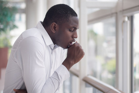 Sick African man coughing; Portrait of ill black man cough due to cold, flu, allergy, polluted air, fine dust, tuberculosis; air pollution, lung cancer, emphysema concept; African man model