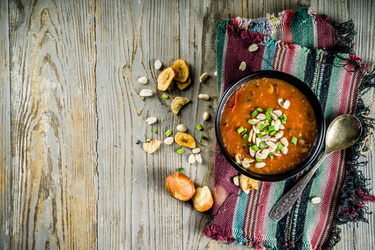 African peanut cream soup with greenery and peanut, wooden background top view copy space