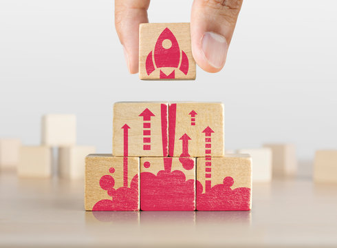 Business start up, start, new project or new idea concept. Wooden blocks with launching rocket graphic arranged in pyramid shape and a man is holding the top one.