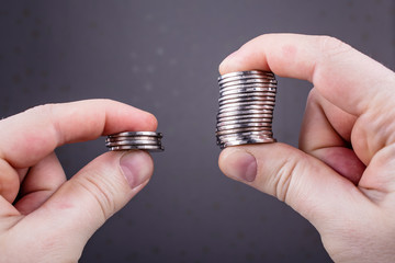 concept with the comparison of two stacks of coins of different sizes in the hands