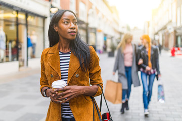 Black woman walking in the city, shopping theme