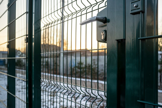 Entrance to the playground of fence and the wicket of the welded wire mesh green color with a metal lock and handle.
