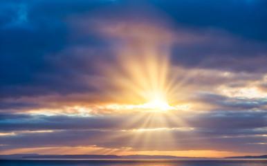 Sun Rays Bursting through Dark Blue Clouds onto the Sea