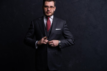 Handsome young business man enjoying a cigarette while standing on black background.