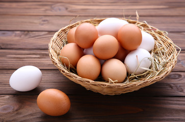 Fresh Chicken eggs in basket on brown background