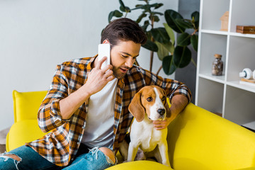 young man talking on smartphone and looking at dog