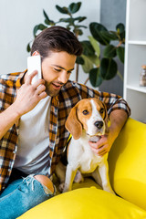 handsome man in checkered shirt talking on smartphone and looking at dog