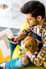 handsome young man using smartphone while sitting on sofa with beagle dog