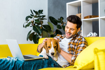 happy young man with laptop petting cute dog on sofa