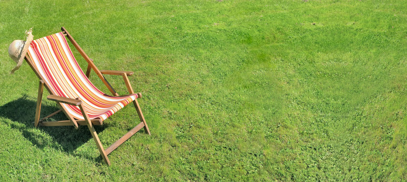 deckchair on greenery grass in a garden in panoramic size