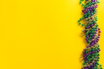 Mardi gras carnival concept - beads on yellow background, top view