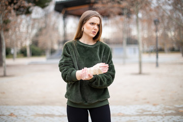 Beautiful young lady in stylish outfit frowning and touching bandage on injured arm while standing in autumn park